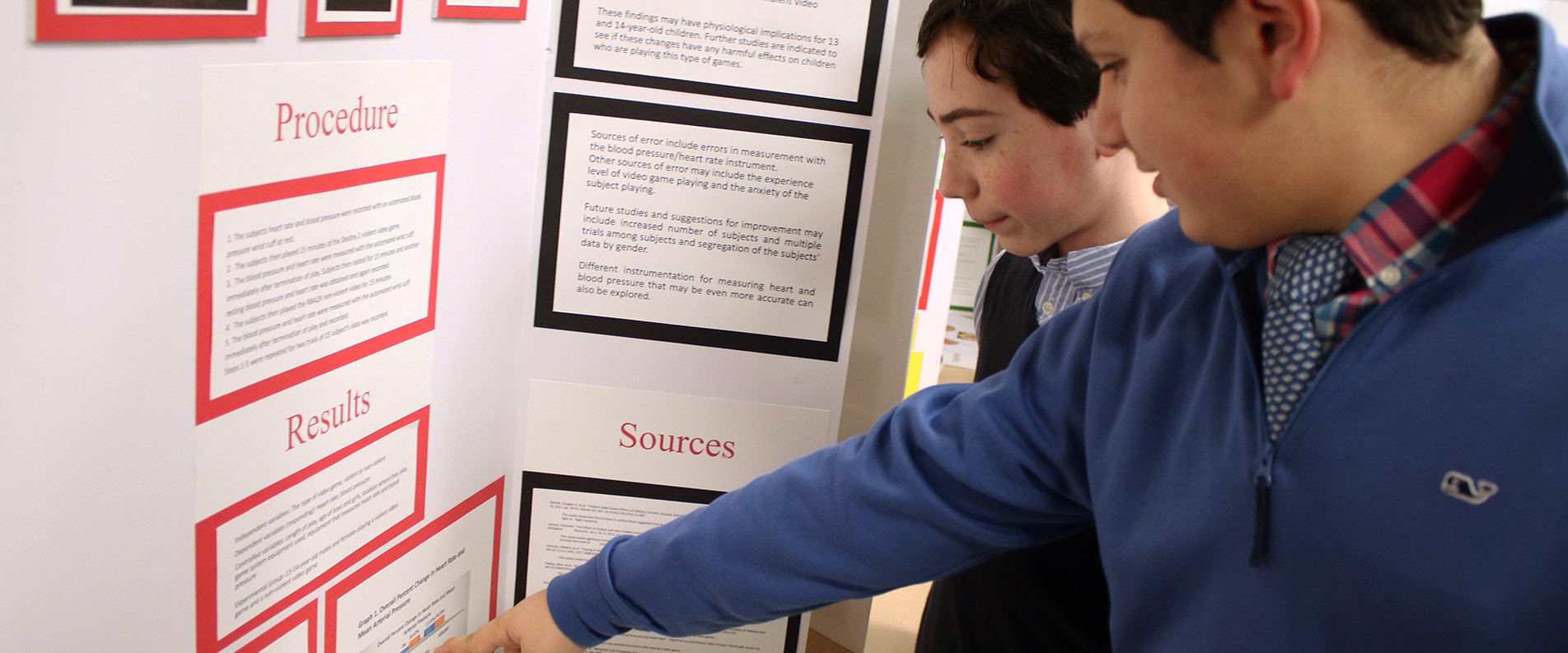 Aquinas Academy middle school students looking at Science Fair presentation board